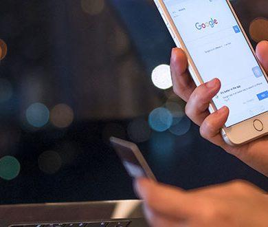 Laptop och mobiltelefon som visar Googles startsida